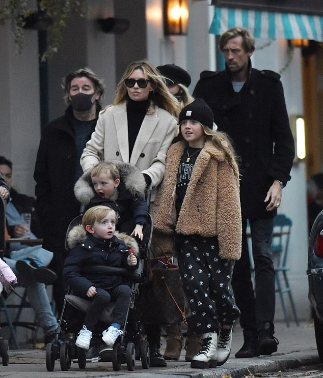Abbey Clancy, cream trench coat, black sweater, black boots, welted pockets, calf length, extra long sleeves, peak lapel collar. Abbey Clancy rocking a cream double breasted trench coat with extra long sleeves, peak lapel collar and welted pockets