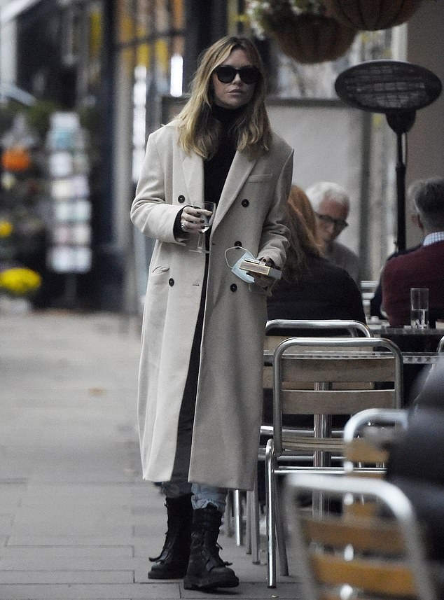 Abbey Clancy rocking a cream double breasted trench coat with extra long sleeves, peak lapel collar and welted pockets