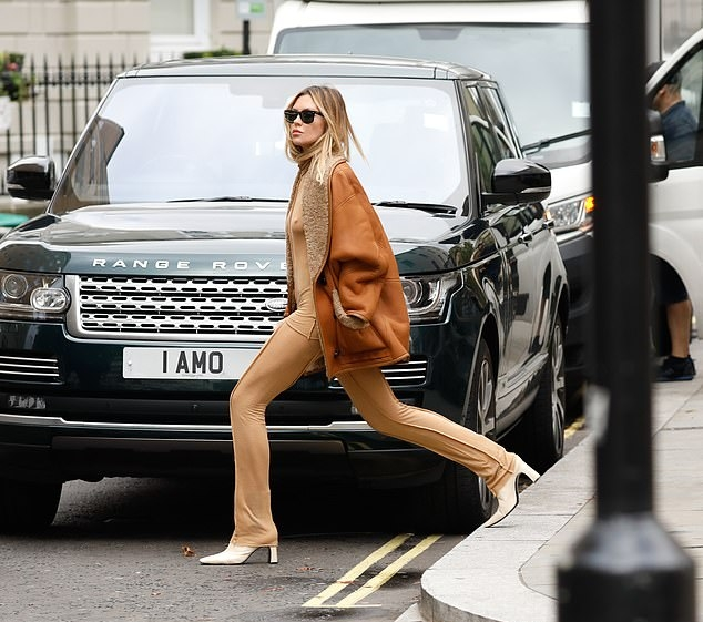 Abbey Clancy, nude sweatshirt, braless, white boots, oversized tan jacket, hip length, casual, black sunglasses, nude trousers, matching. Abbey Clancy wearing a nude sweatshirt