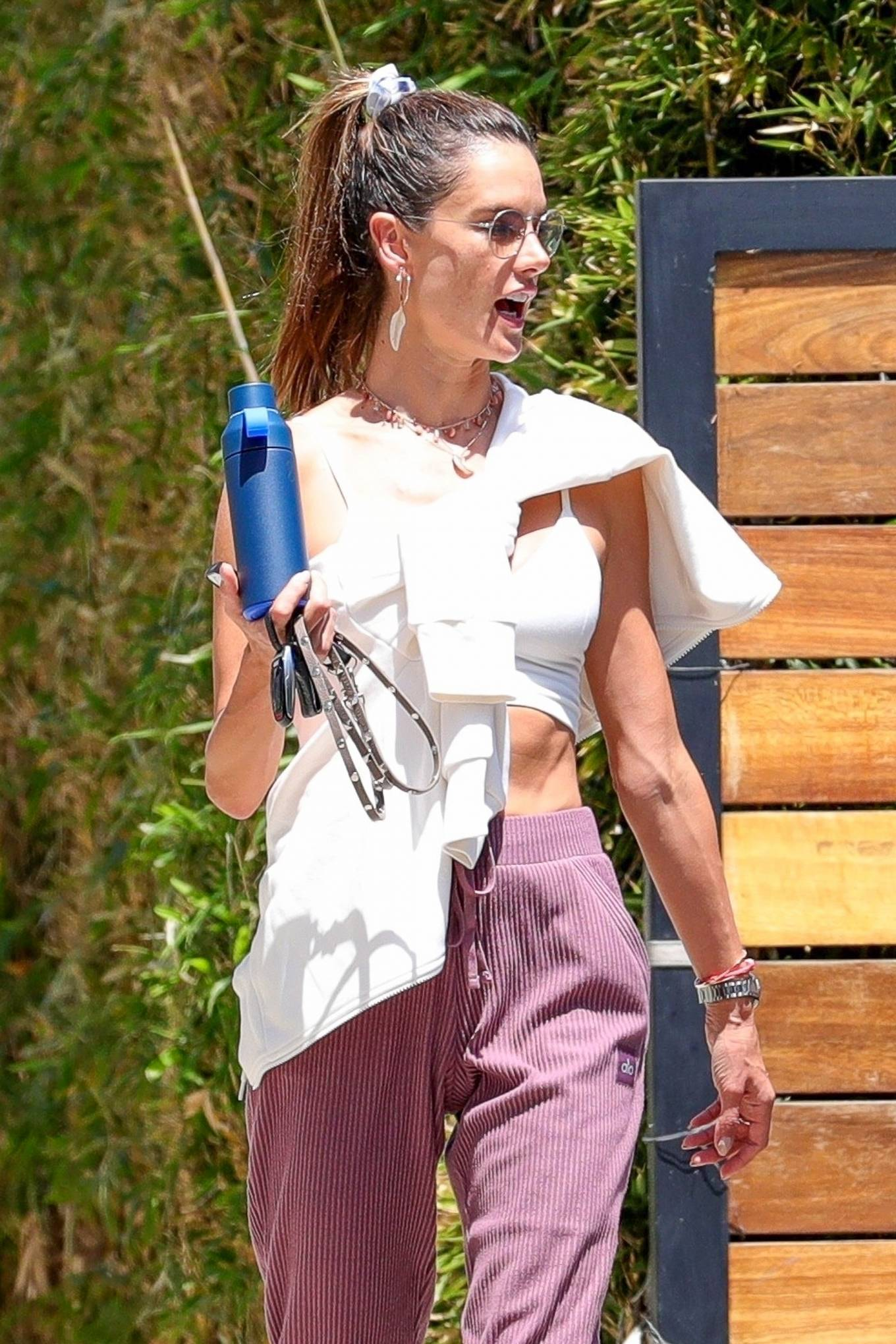 Alessandra Ambrosio wearing round white Adidas lace-up sneakers with flat heel