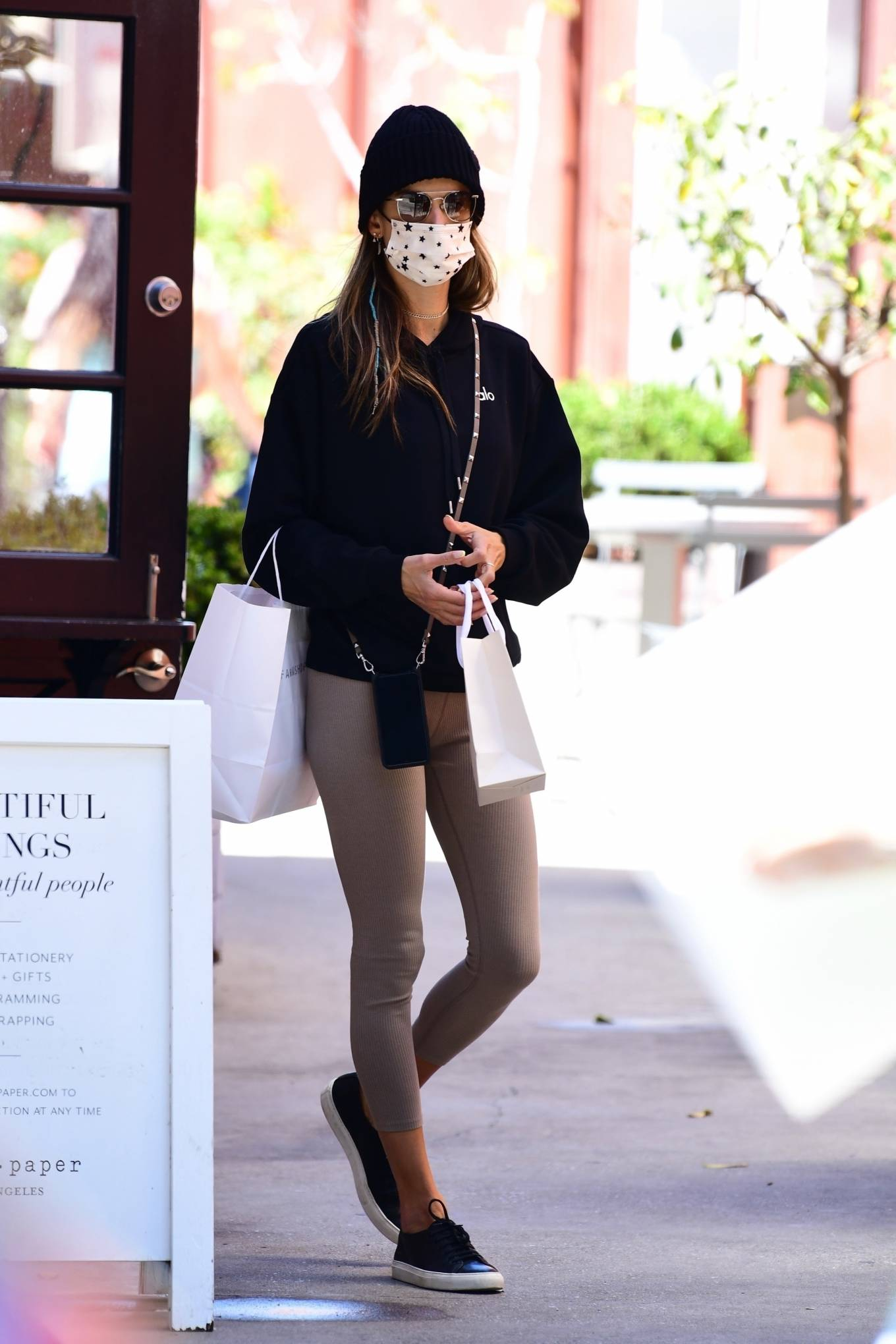 Alessandra Ambrosio wearing round black white lace-up sneakers by Common Projects with flat heel