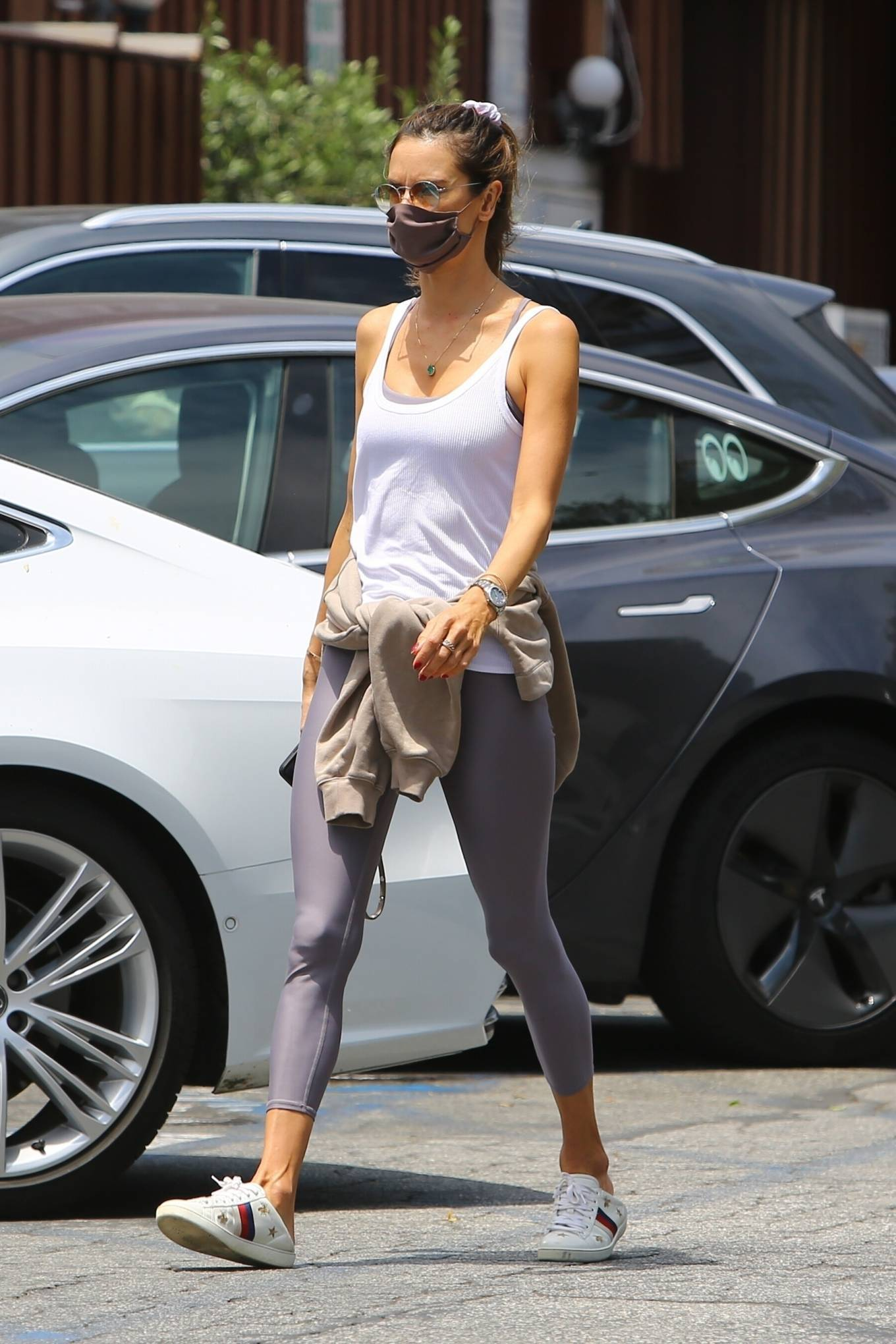 Alessandra Ambrosio rocking embroidered white Gucci lace-up sneakers with flat heel and brand logo