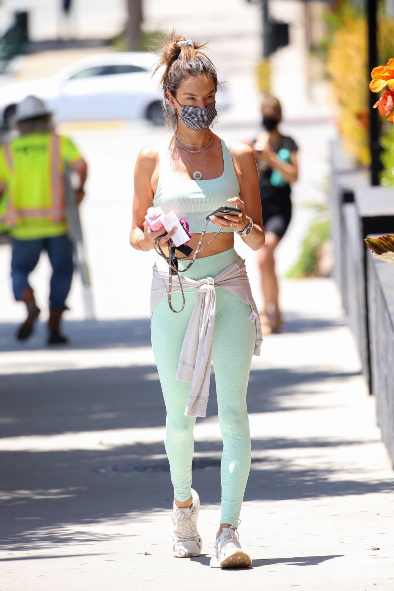 Alessandra Ambrosio donning round white grey lace-up sneakers with flat heel
