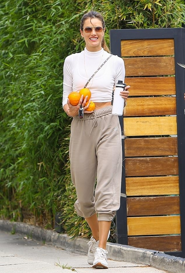Alessandra Ambrosio donning round golden white lace-up sneakers by New Balance with chunky sole