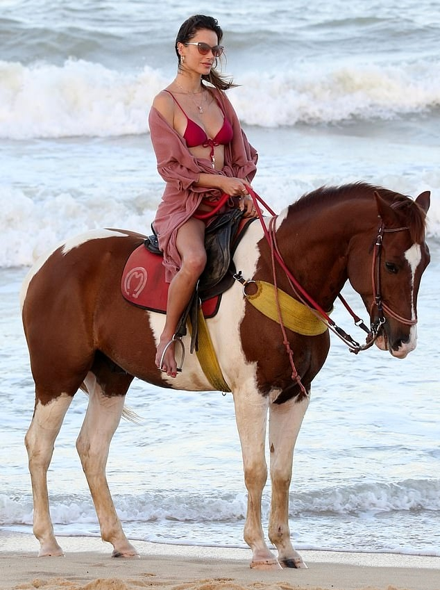 Alessandra Ambrosio wearing a skimpy deep pink bikini top with sea shell ornaments, a scoop neck and spaghetti straps