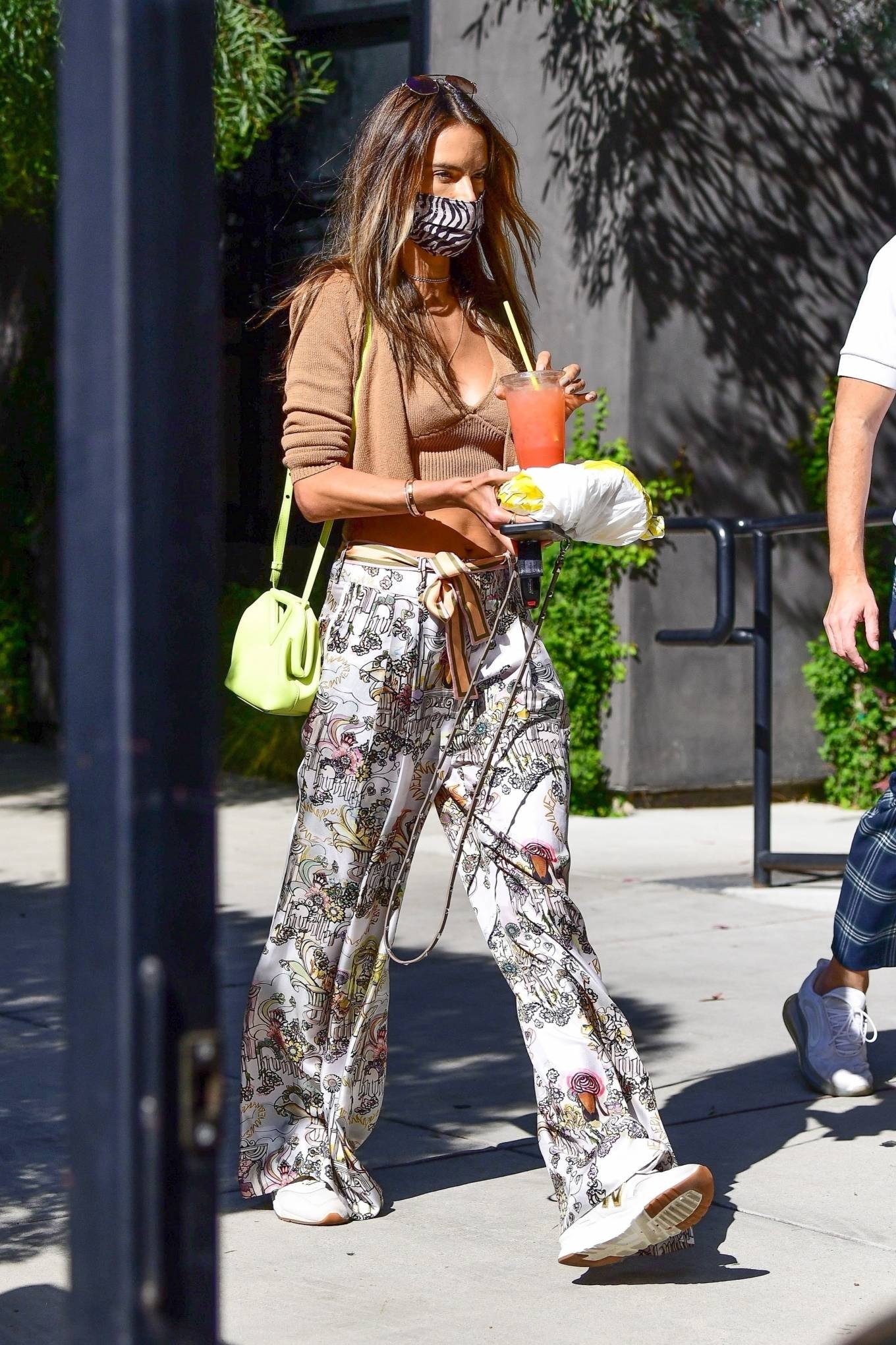 Alessandra Ambrosio, New Balance sneakers, golden sneakers, brown cardigan, Bottega Veneta shoulder bag, chunky sole, round, lace-up, white sneakers, brown camisole, brown Vehla sunglasses, white Zimmermann palazzo. Alessandra Ambrosio donning round golden white lace-up sneakers by New Balance with chunky sole