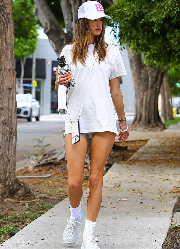 Alessandra Ambrosio donning round white Nike lace-up sneakers with chunky heel