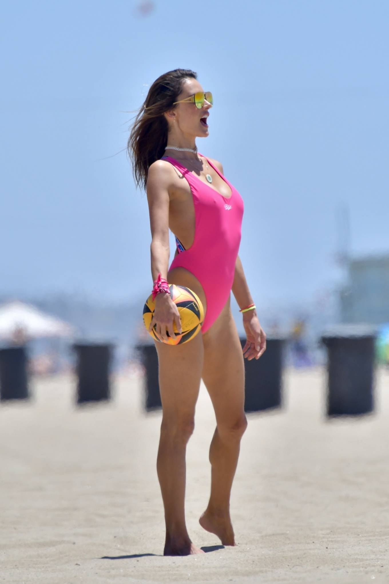 Alessandra Ambrosio wearing a figure hugging bodysuit with criss cross back, logo band and a scoop neck