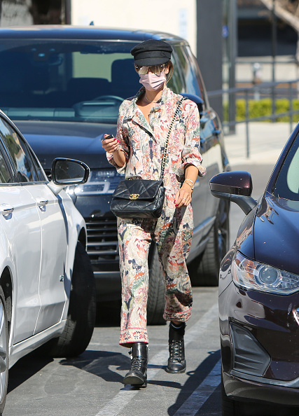 Alessandra Ambrosio, cotton, black Saint Laurent boots, tied waist, relaxed fit, floral, rolled sleeves, shirt collar, printed, V-neck, button front. Alessandra Ambrosio rocking a relaxed fit cotton jumpsuit with rolled sleeves, shirt collar, floral print, a V-neck and tied waist