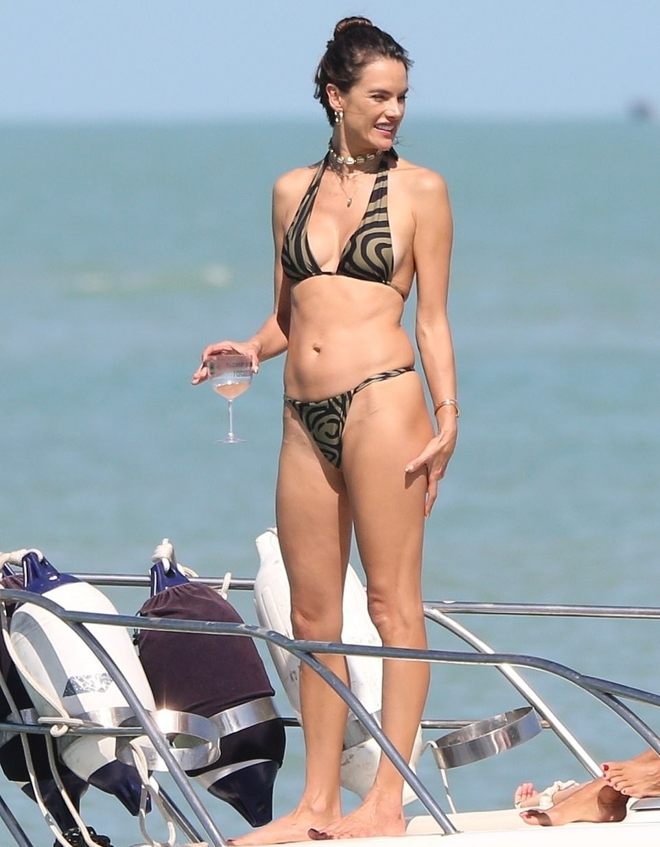 Alessandra Ambrosio rocking a skimpy bi color bikini top with a halter neck and straps tied at the shoulder