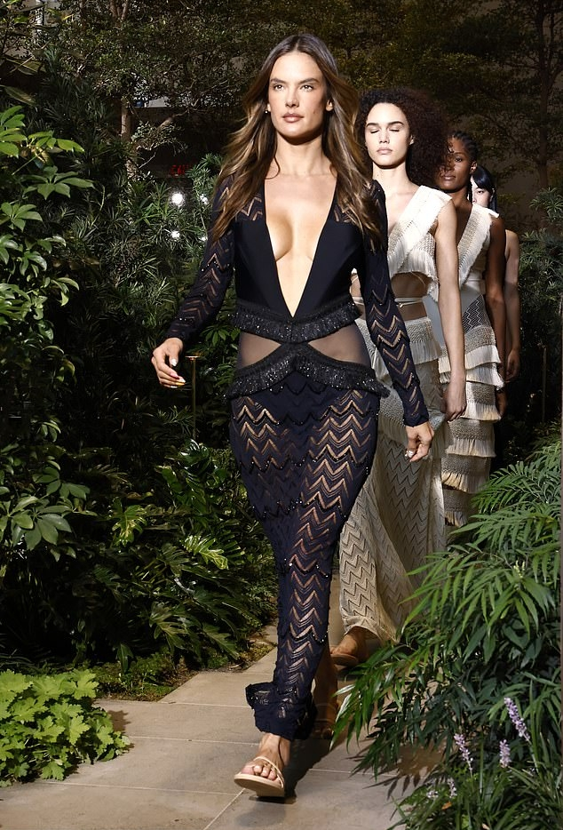 Alessandra Ambrosio donning a semi-sheer shimmery black dress with full sleeves, sheer cut outs at the waist and plunging neckline that almost went down to her waist