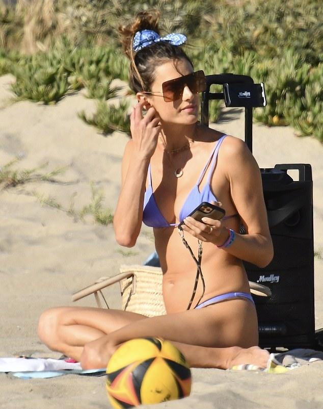 Alessandra Ambrosio rocking a plunging blue bikini top with a nylon material, strappy and spaghetti straps