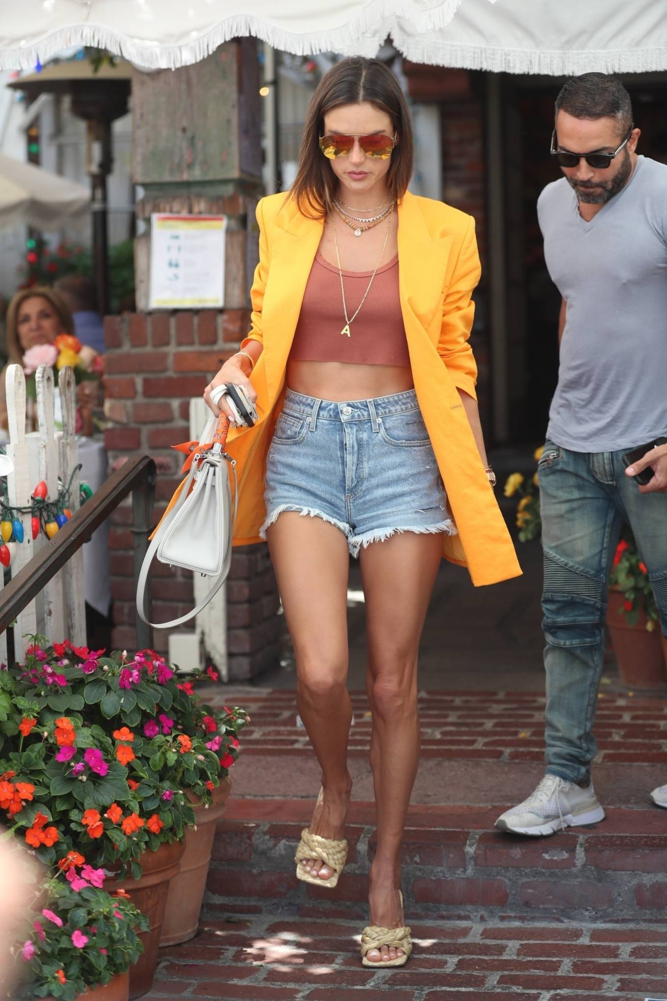 Alessandra Ambrosio donning fitted blue ripped shorts with torn hem