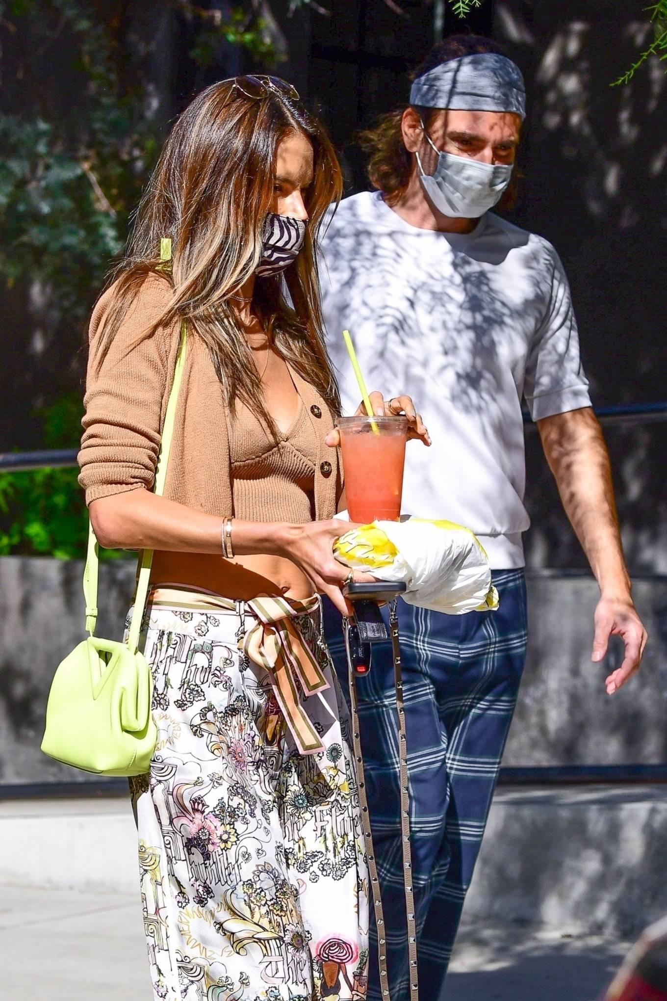 Alessandra Ambrosio, New Balance  sneakers, golden  sneakers, brown cardigan, Bottega Veneta shoulder bag, round, lace-up, chunky sole, white  sneakers, brown camisole, brown Vehla sunglasses, white Zimmermann palazzo