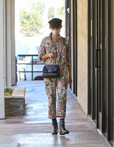 Alessandra Ambrosio rocking a relaxed fit cotton jumpsuit with rolled sleeves, shirt collar, floral print, a V-neck and tied waist