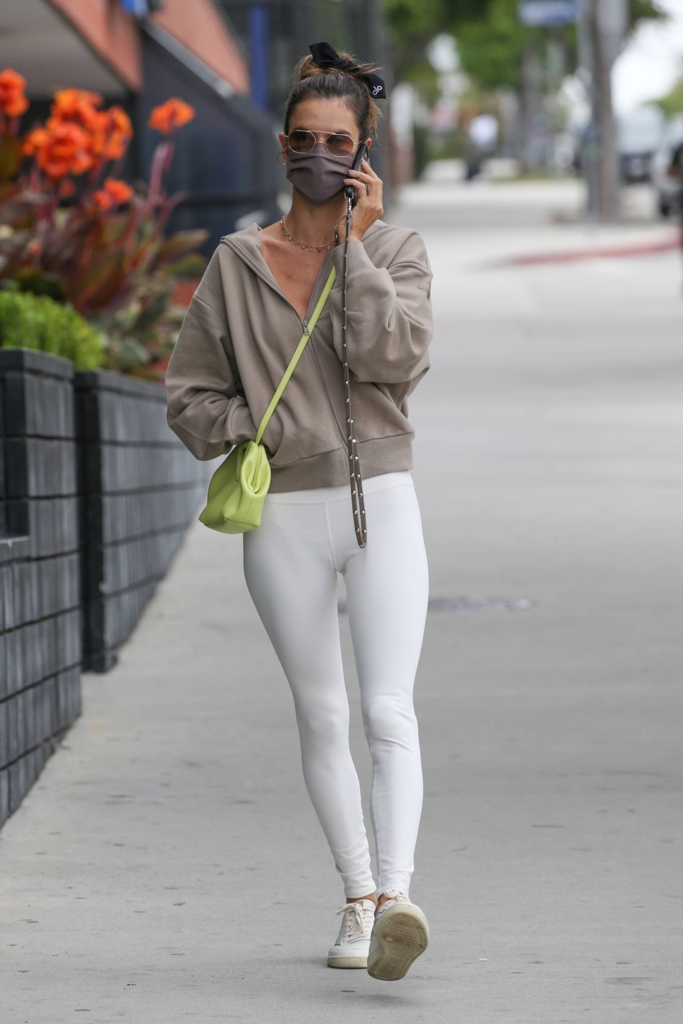 Alessandra Ambrosio rocking round white beige lace-up sneakers with flat heel
