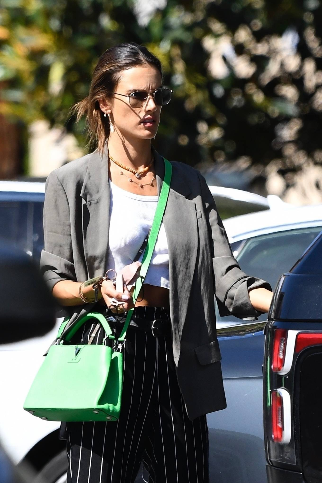 Alessandra Ambrosio rocking brand logo white black lace-up sneakers by New Balance with chunky sole