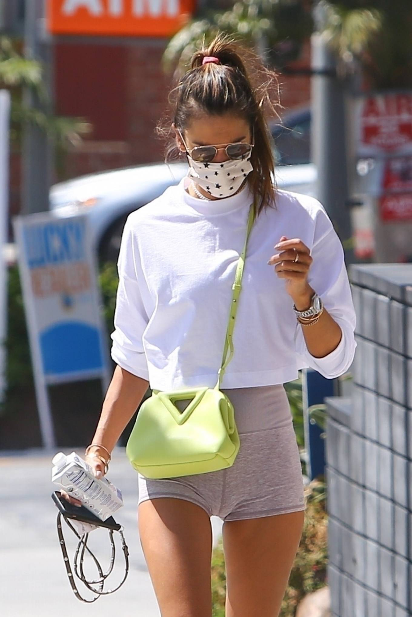 Alessandra Ambrosio, white sneakers, white crop top, Bottega Veneta shoulder bag, round, lace-up, black sunglasses. Alessandra Ambrosio donning round white lace-up sneakers