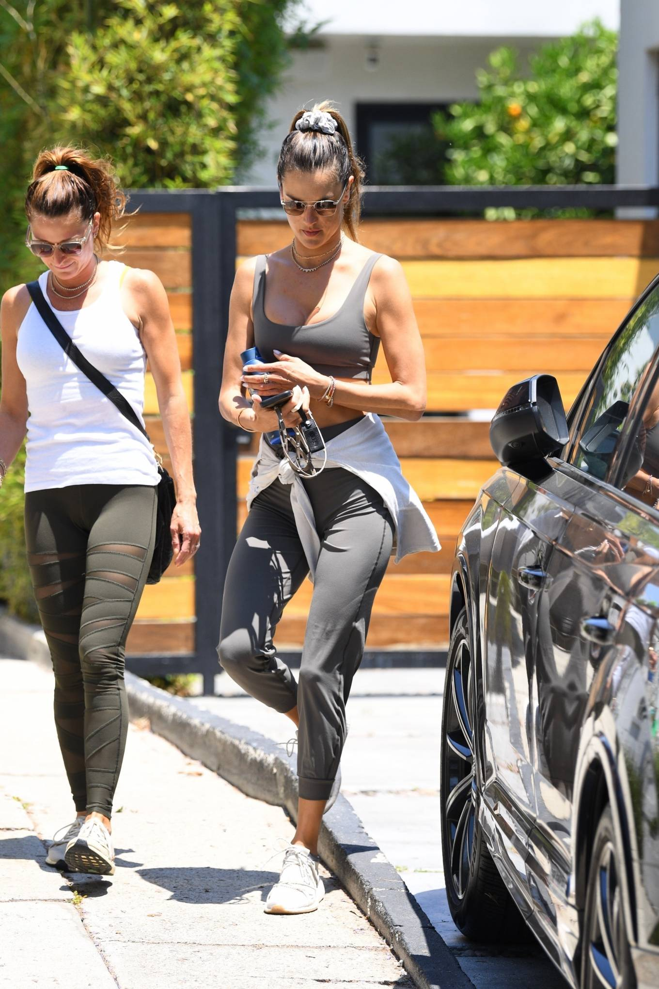 Alessandra Ambrosio wearing a relaxed fit white pullover with rolled sleeves and a crew neck
