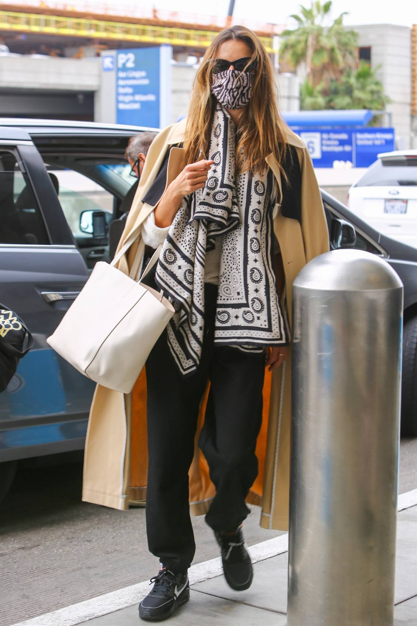 Alessandra Ambrosio rocking brand logo black Nike lace-up sneakers with flat heel