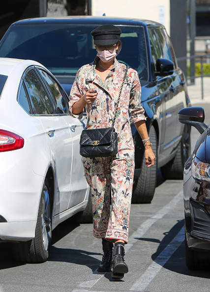 Alessandra Ambrosio, cotton, black Saint Laurent boots, relaxed fit, floral, rolled sleeves, tied waist, printed, shirt collar, button front, V-neck. Alessandra Ambrosio rocking a relaxed fit cotton jumpsuit with rolled sleeves, shirt collar, floral print, a V-neck and tied waist