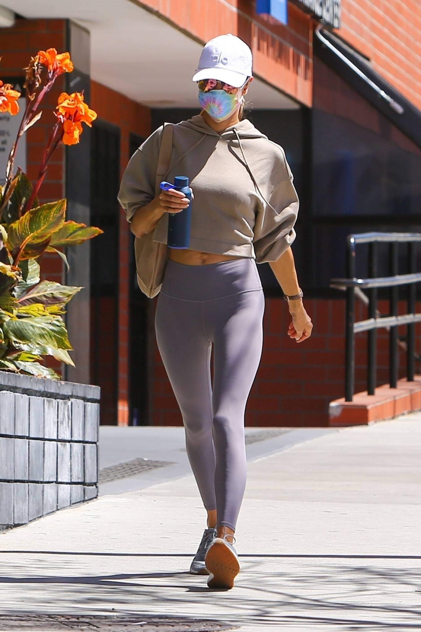 Alessandra Ambrosio donning round rose gold light blue lace-up sneakers by New Balance with chunky sole