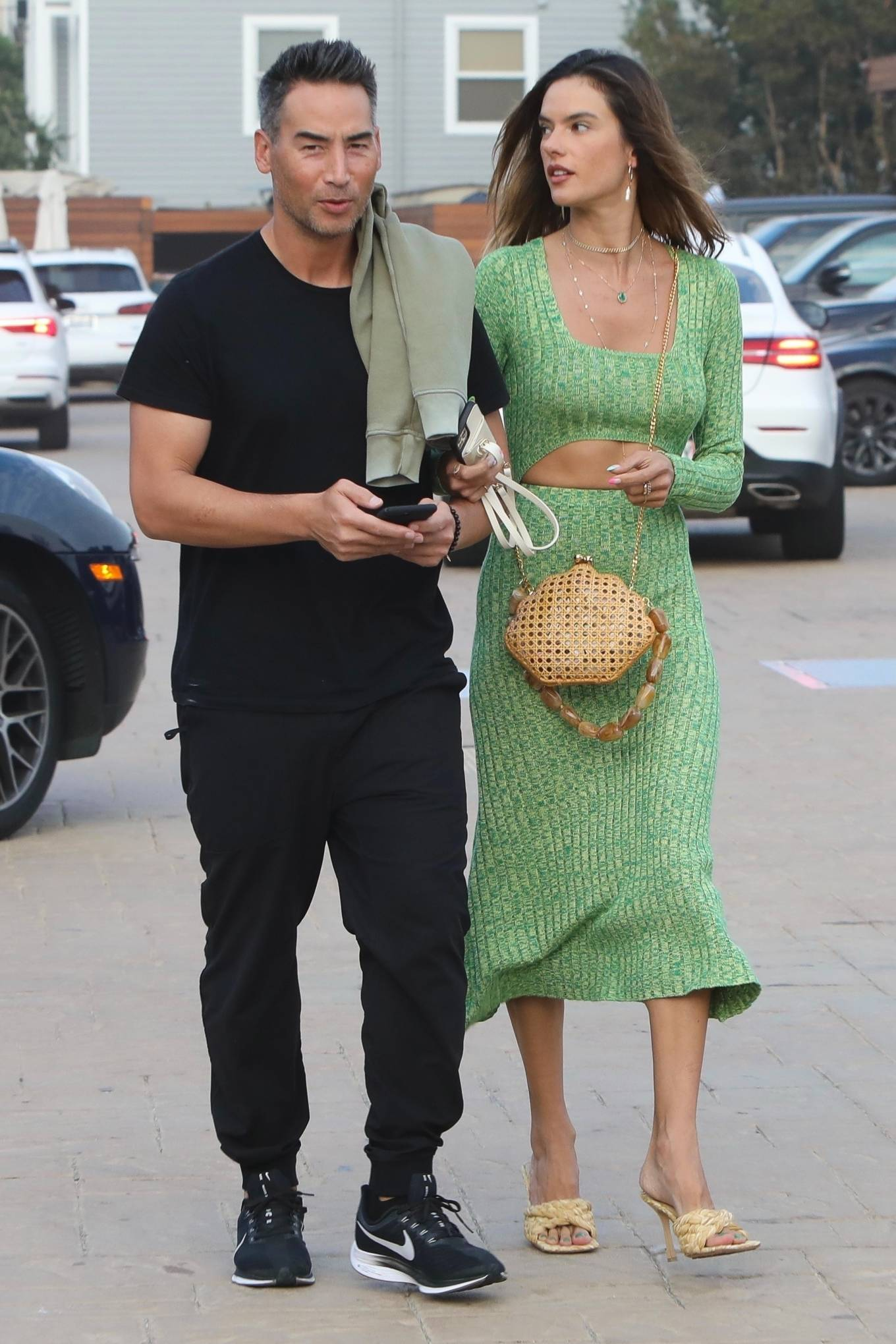Alessandra Ambrosio rocking a figure hugging leaf green dress with a knit fabric, full sleeves, cut out and a square neck