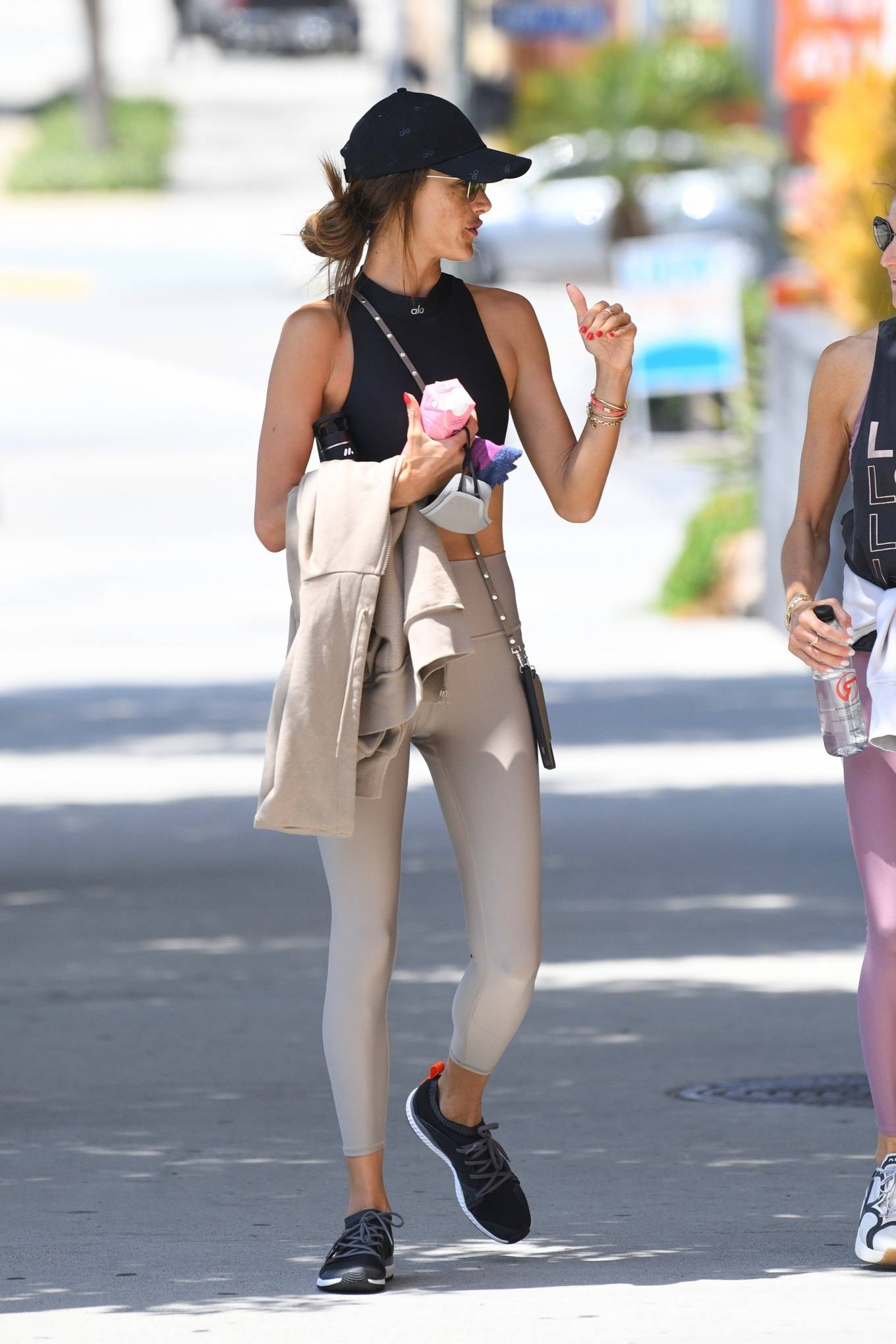Alessandra Ambrosio rocking round black lace-up sneakers with flat heel