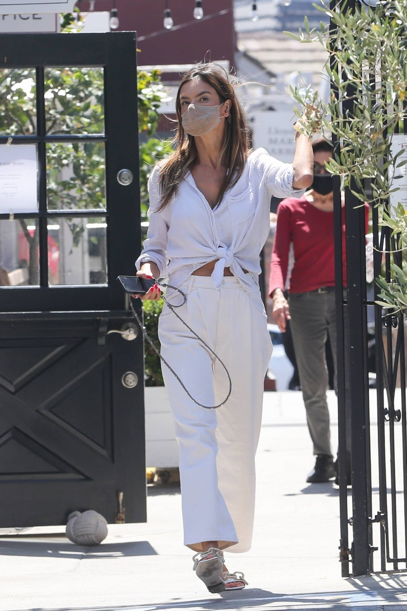 Alessandra Ambrosio donning round white slip on sandals with flat heel