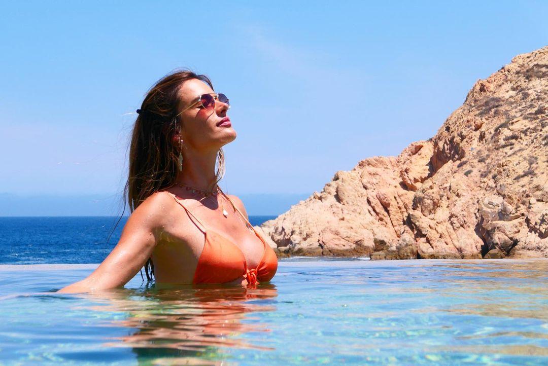 Alessandra Ambrosio rocking a skimpy orange bikini top with tie back, a V-neck and spaghetti straps