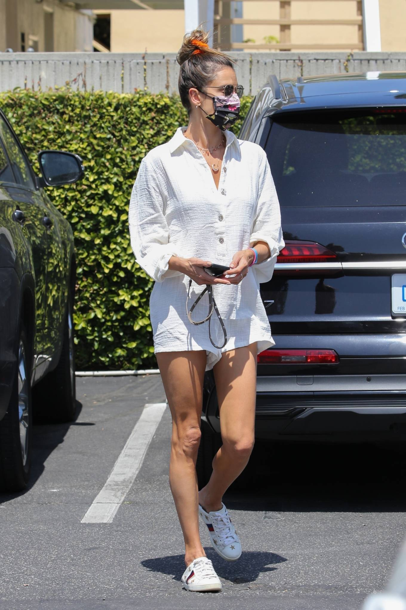 Alessandra Ambrosio donning embroidered white Gucci lace-up sneakers with flat heel and brand logo