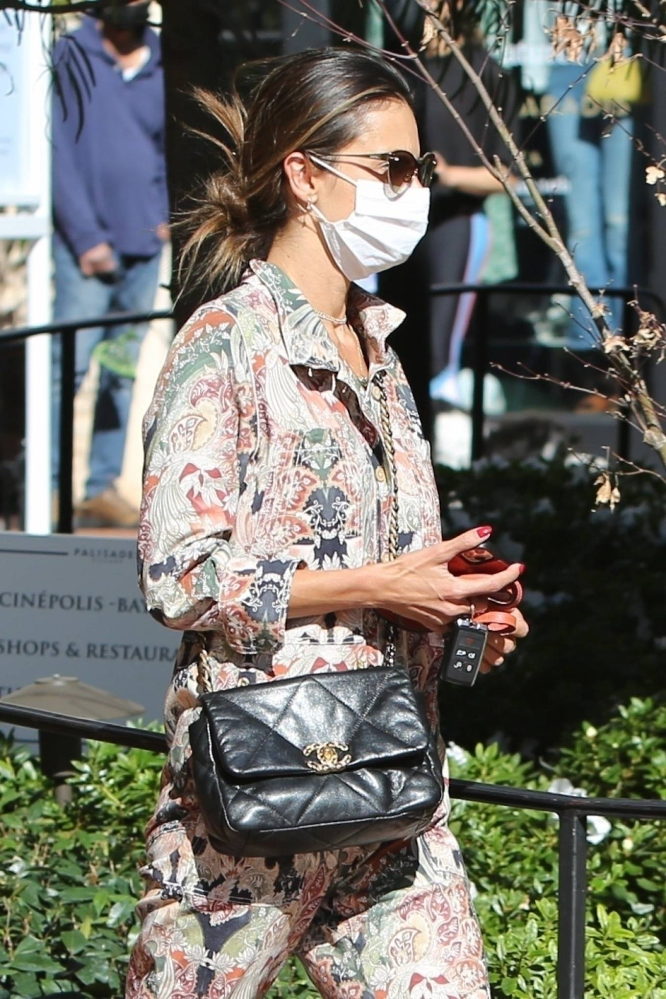 Alessandra Ambrosio, cotton, black Saint Laurent boots, rolled sleeves, tied waist, relaxed fit, floral, shirt collar, printed, V-neck, button front. Alessandra Ambrosio rocking a relaxed fit cotton jumpsuit with rolled sleeves, shirt collar, floral print, a V-neck and tied waist
