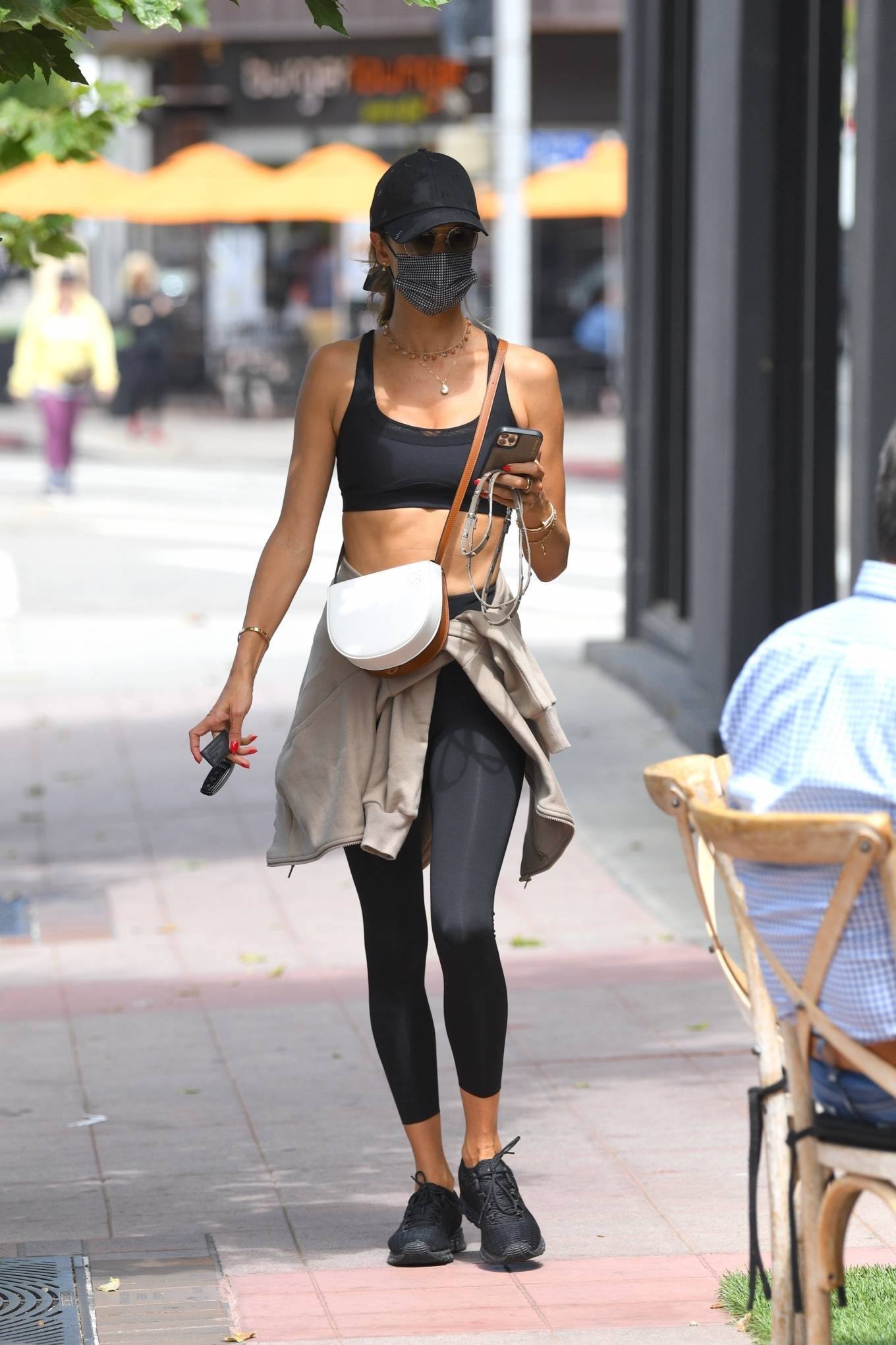 Alessandra Ambrosio wearing round black Asics lace-up sneakers with flat heel