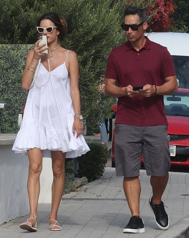 Alessandra Ambrosio donning strappy white slingback sandals with flat heel