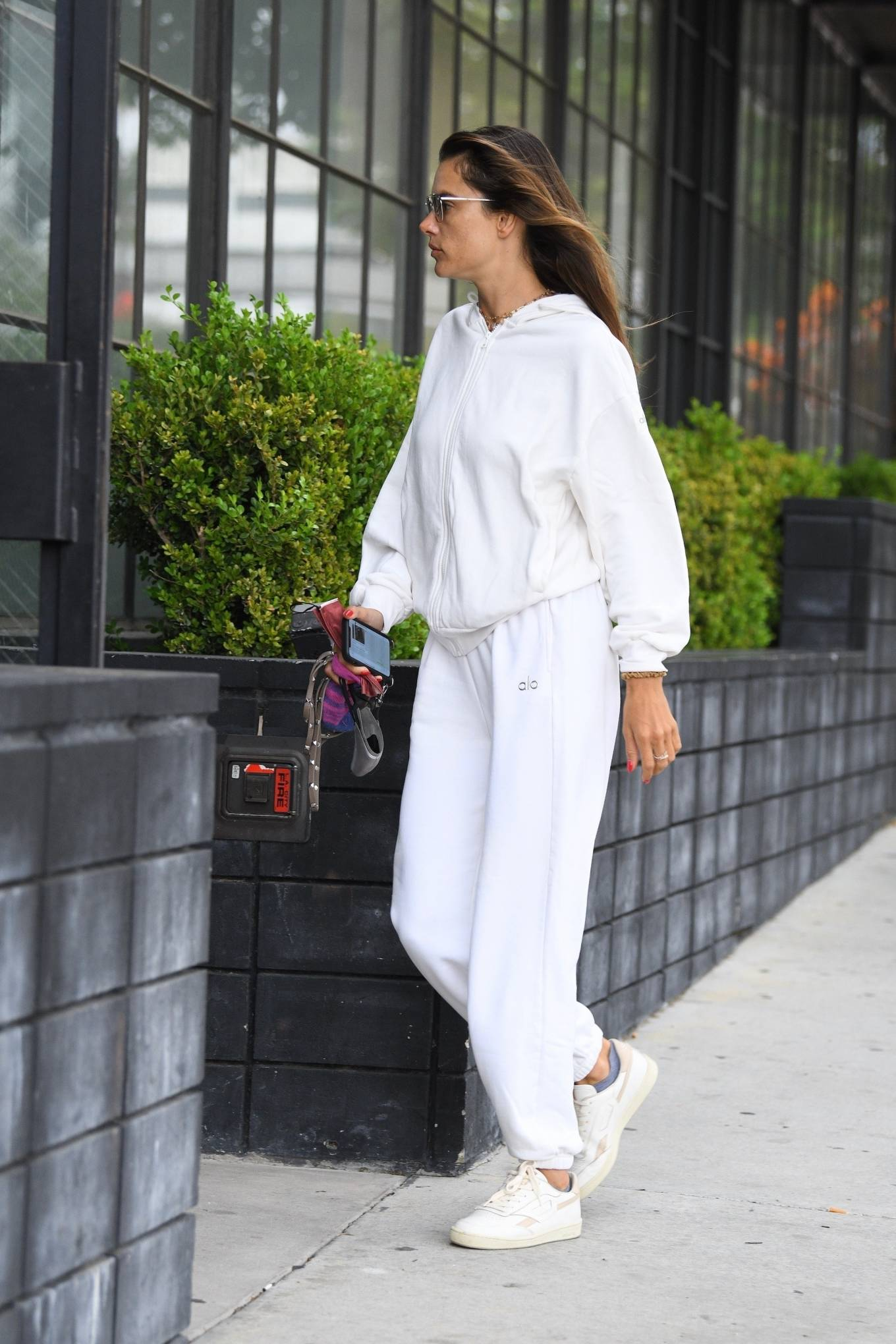 Alessandra Ambrosio wearing brand logo white lace-up sneakers with flat heel