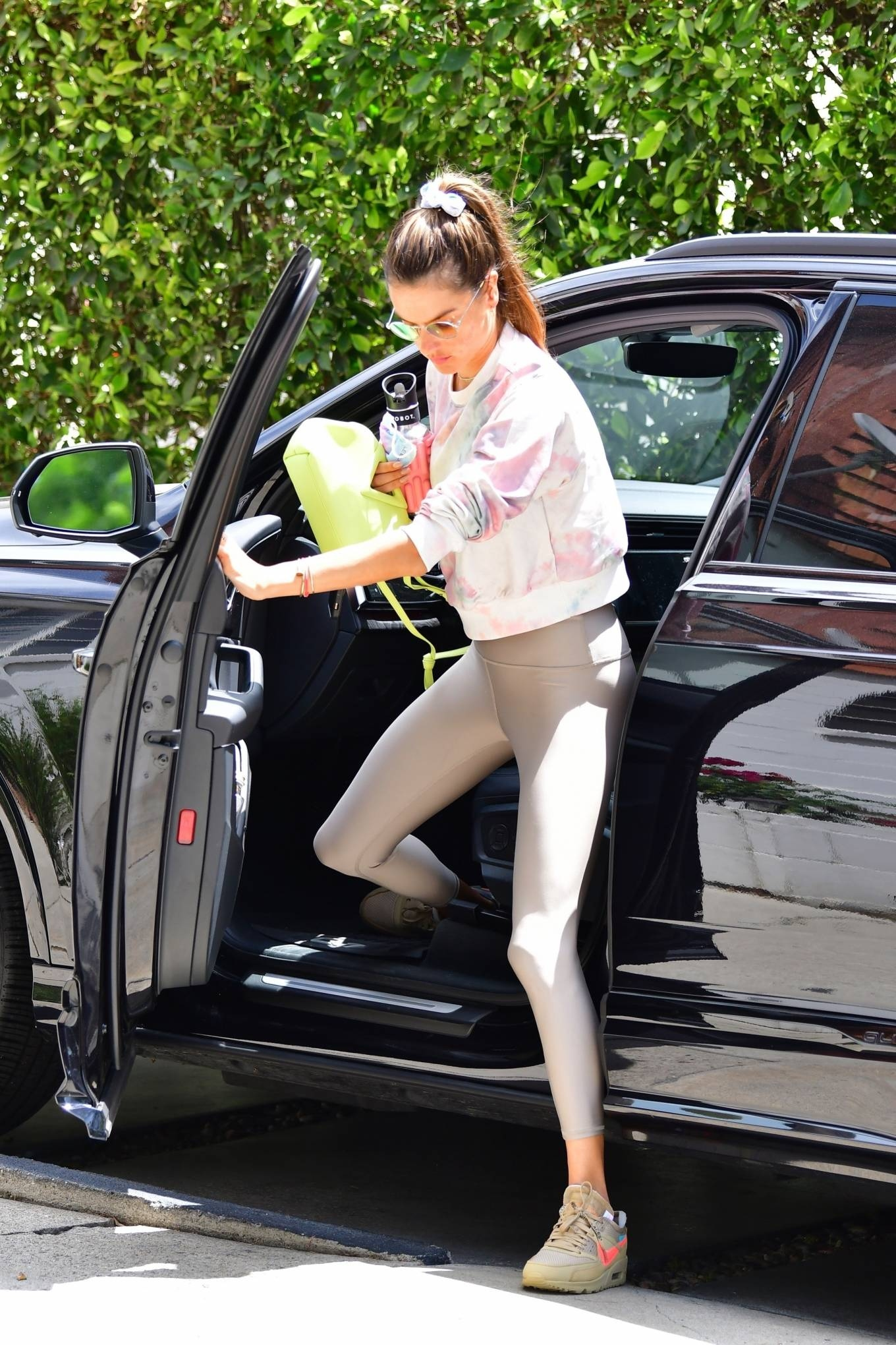 Alessandra Ambrosio donning brand logo Nude brown lace-up sneakers by Nike with flat heel