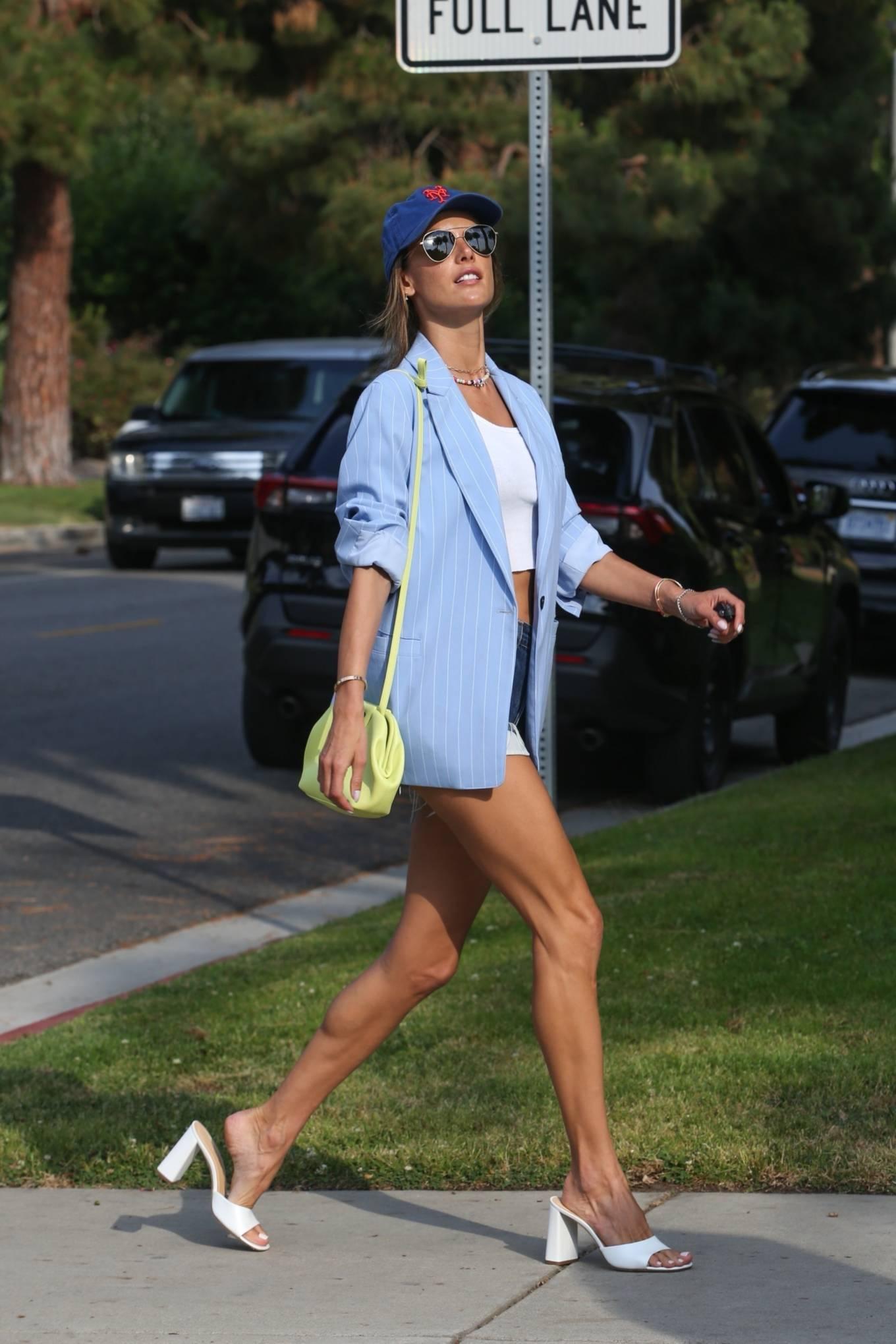 Alessandra Ambrosio, white slippers, yellow blazer, black sunglasses, round, open toe, white crop top. Alessandra Ambrosio wearing round white open toe slippers