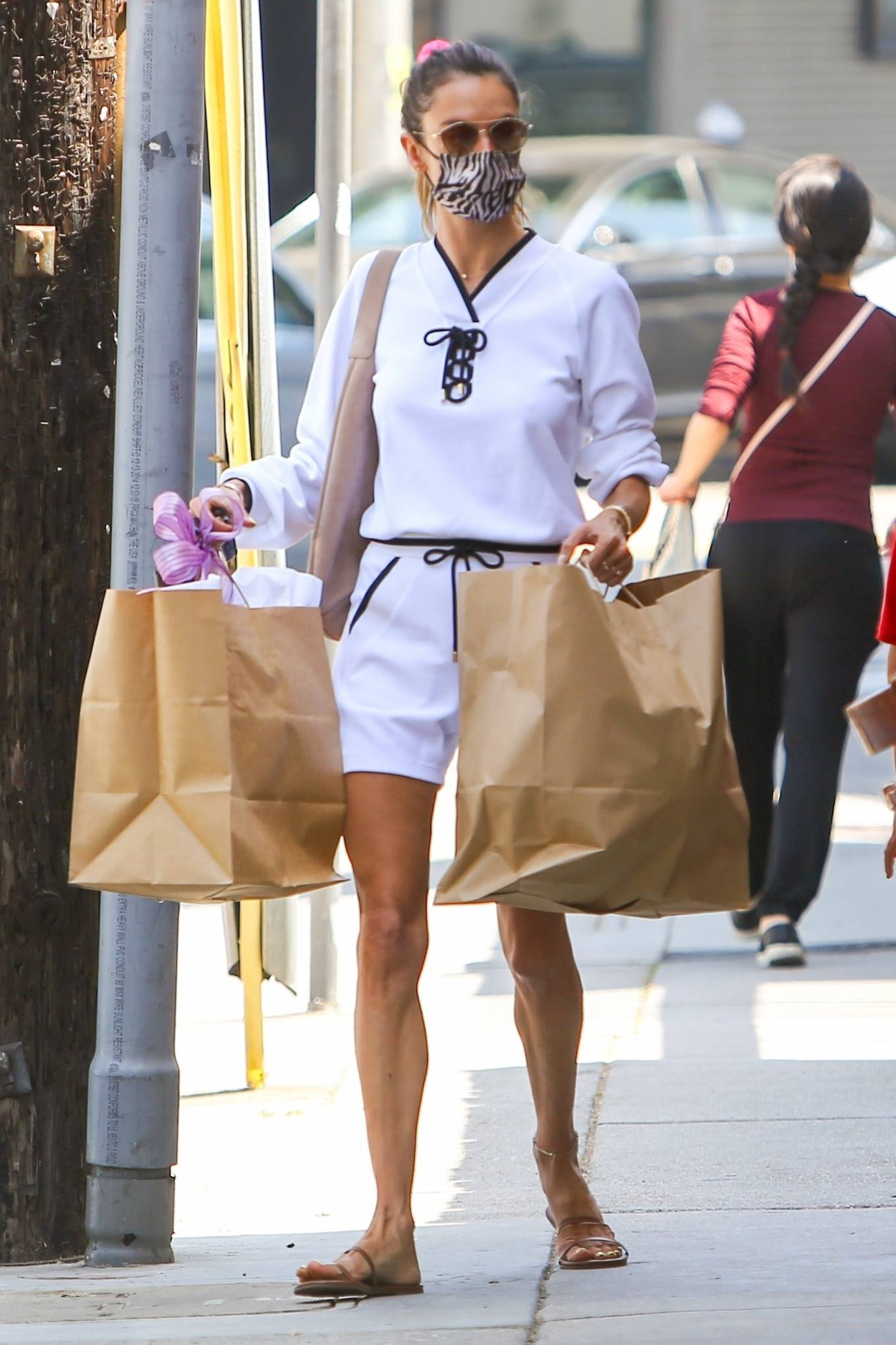Alessandra Ambrosio wearing a relaxed fit white sweatshirt with rolled sleeves