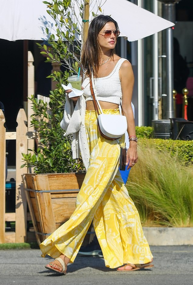 Alessandra Ambrosio donning strappy white cross strap sandals with flat heel