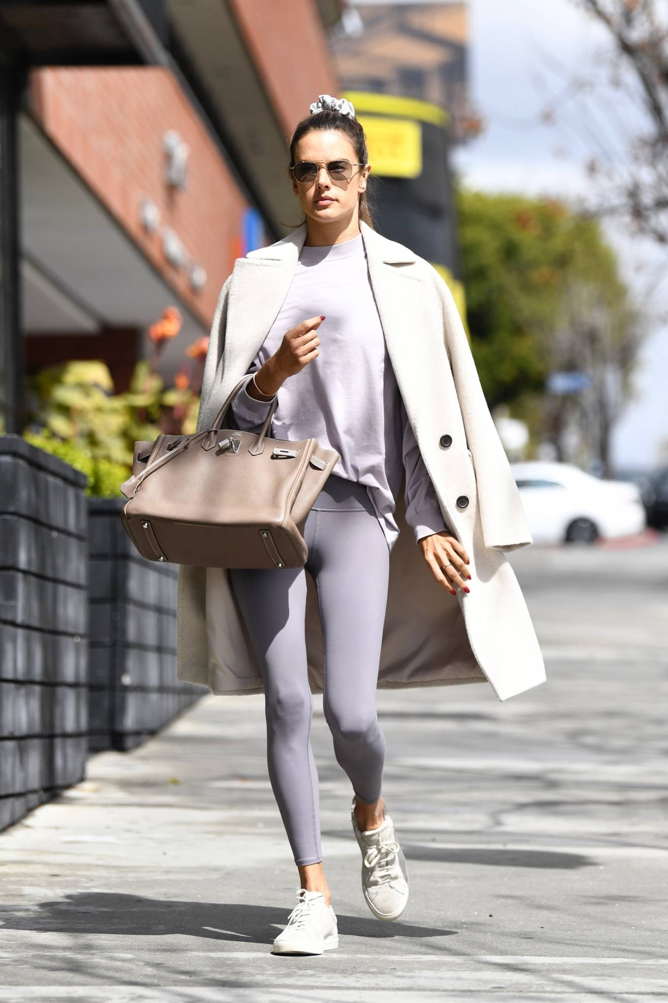 Alessandra Ambrosio rocking round white suede lace-up sneakers by Common Projects with flat heel