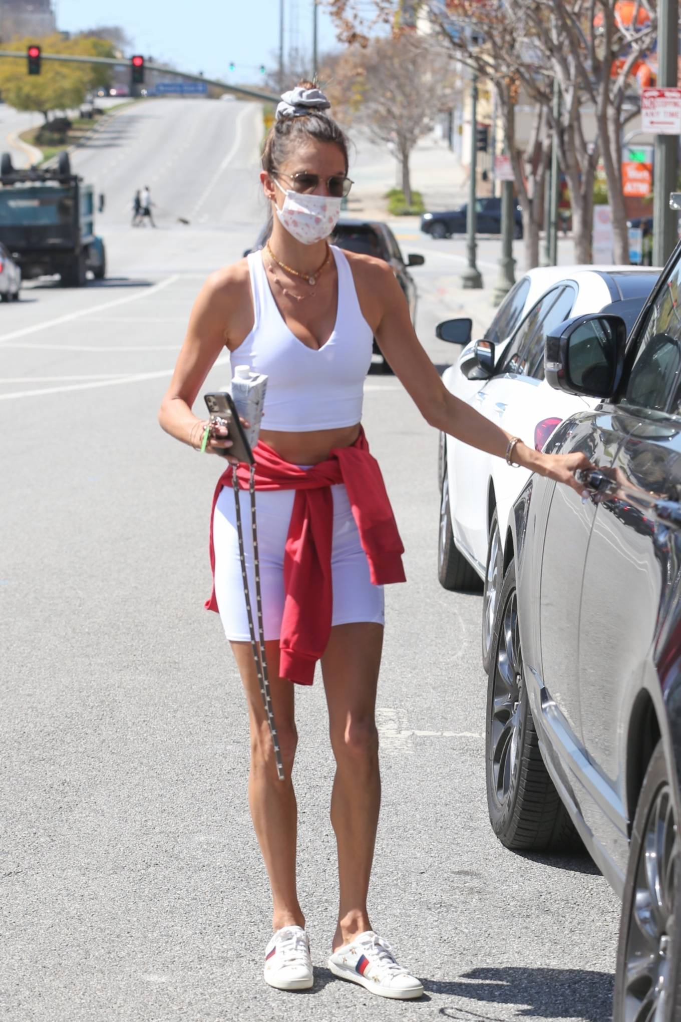 Alessandra Ambrosio wearing embroidered white Gucci lace-up sneakers with collapsible heel and brand logo