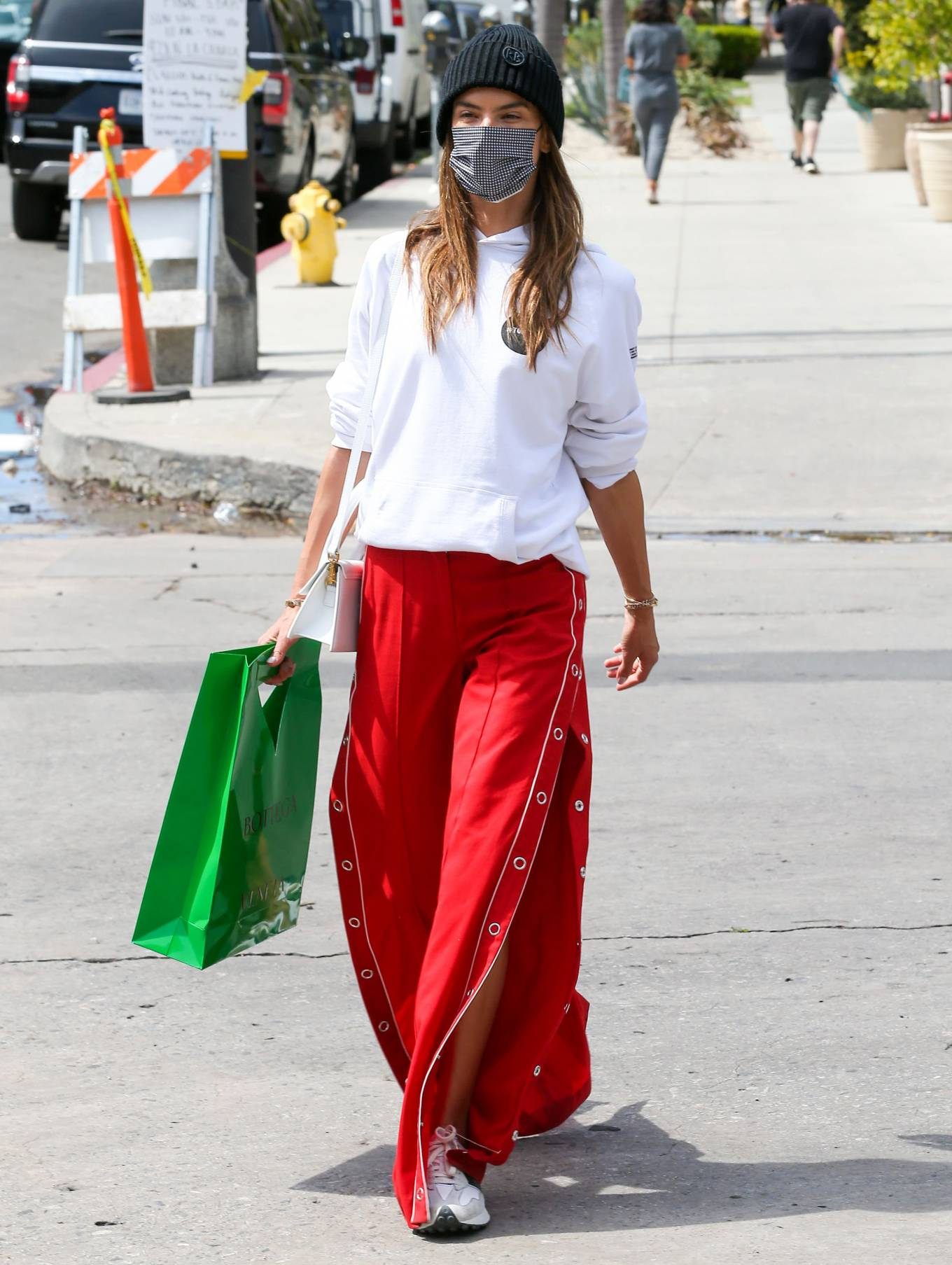 Alessandra Ambrosio, New Balance sneakers, white and black sneakers, white Jacquemus shoulder bag, oversized white hoodie, round, lace-up, flat heel, red trousers, brand logo. Alessandra Ambrosio wearing brand logo white and black lace-up sneakers by New Balance with flat heel