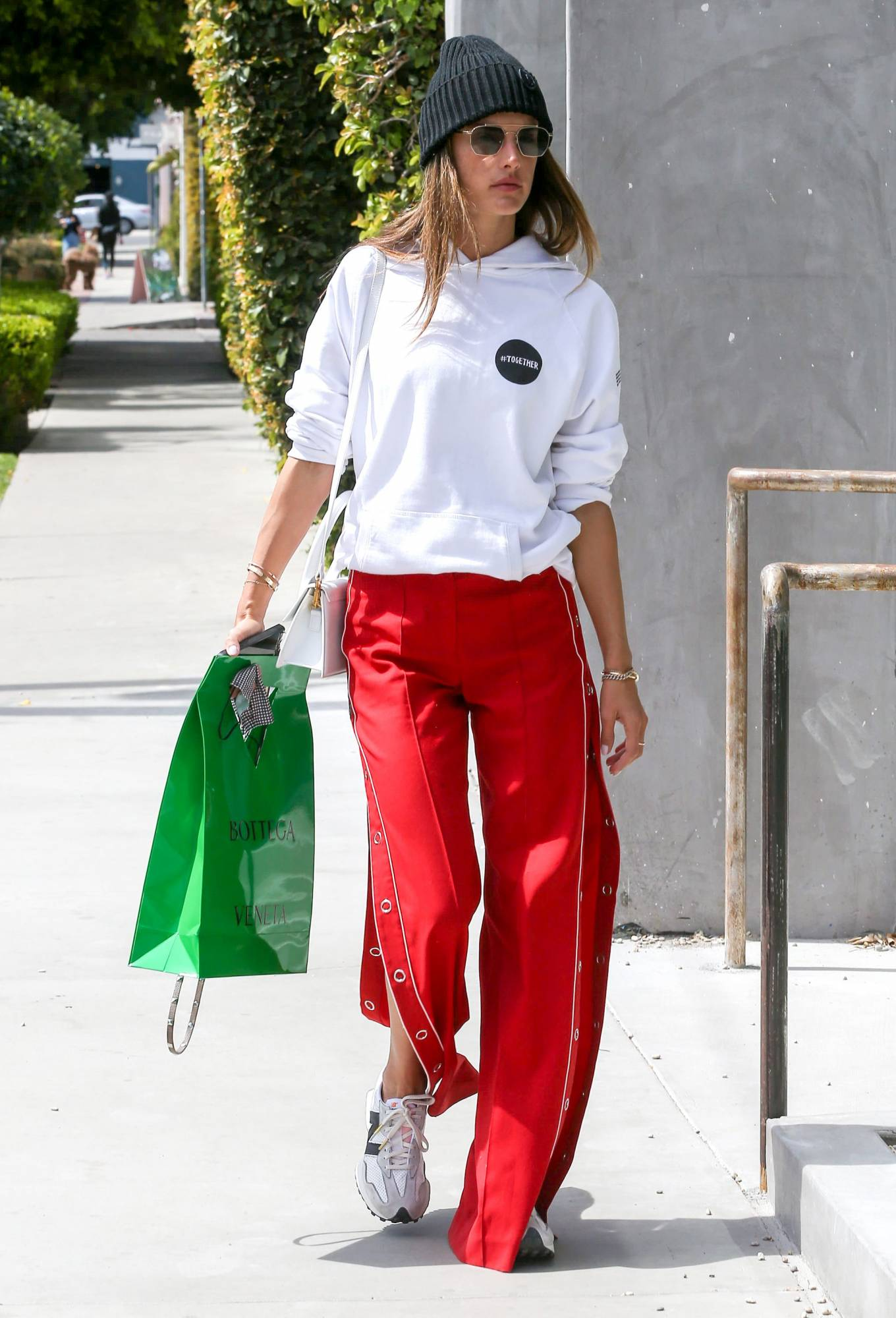 Alessandra Ambrosio wearing brand logo white and black lace-up sneakers by New Balance with flat heel