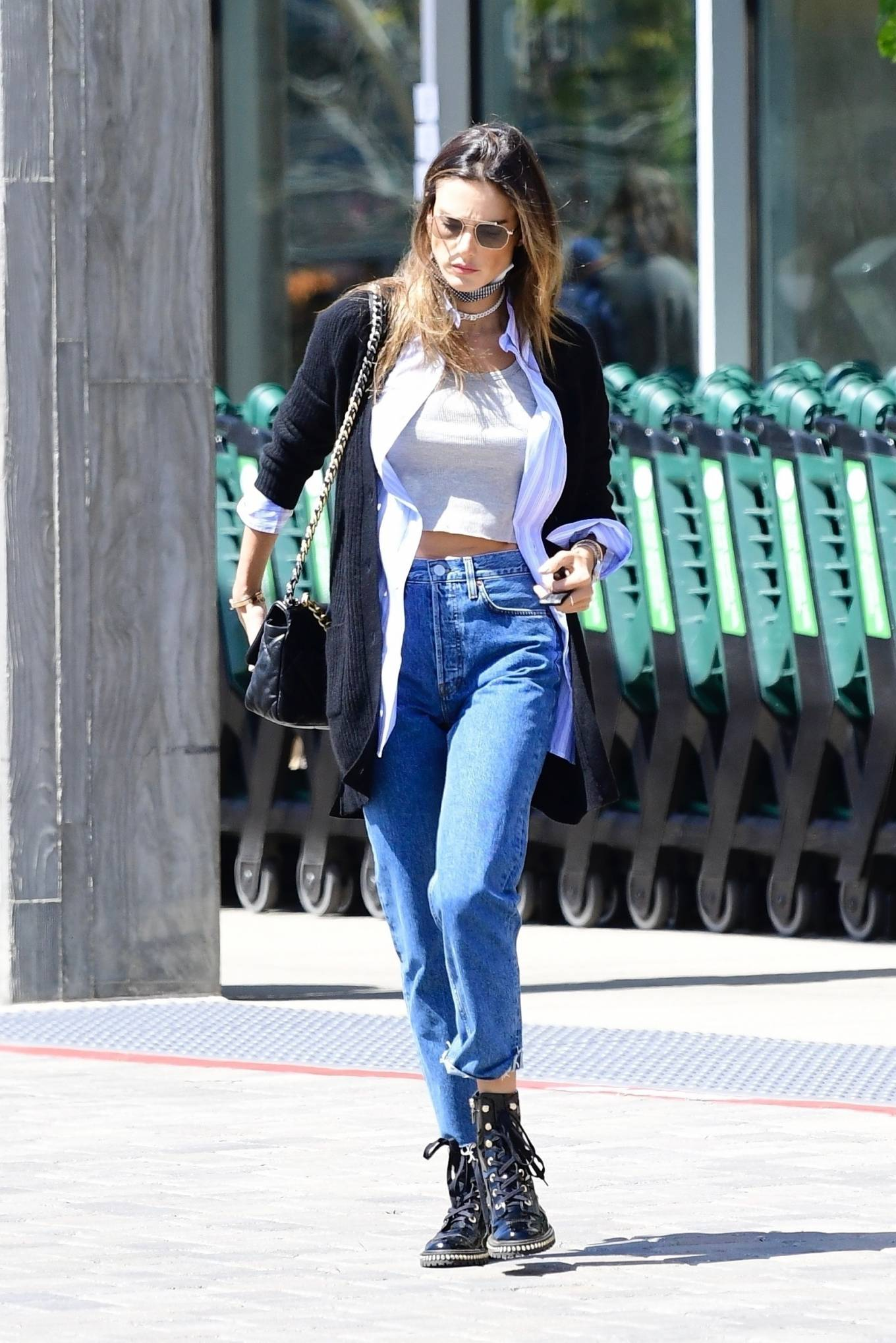 Alessandra Ambrosio, Schutz boots, black boots, lilac shirt, black Chanel purse, patent-leather, round, lace-up, block heel, grey crop top, black sunglasses, ankle, dark blue jeans, zip up. Alessandra Ambrosio wearing round black patent-leather ankle boots by Schutz with block heel