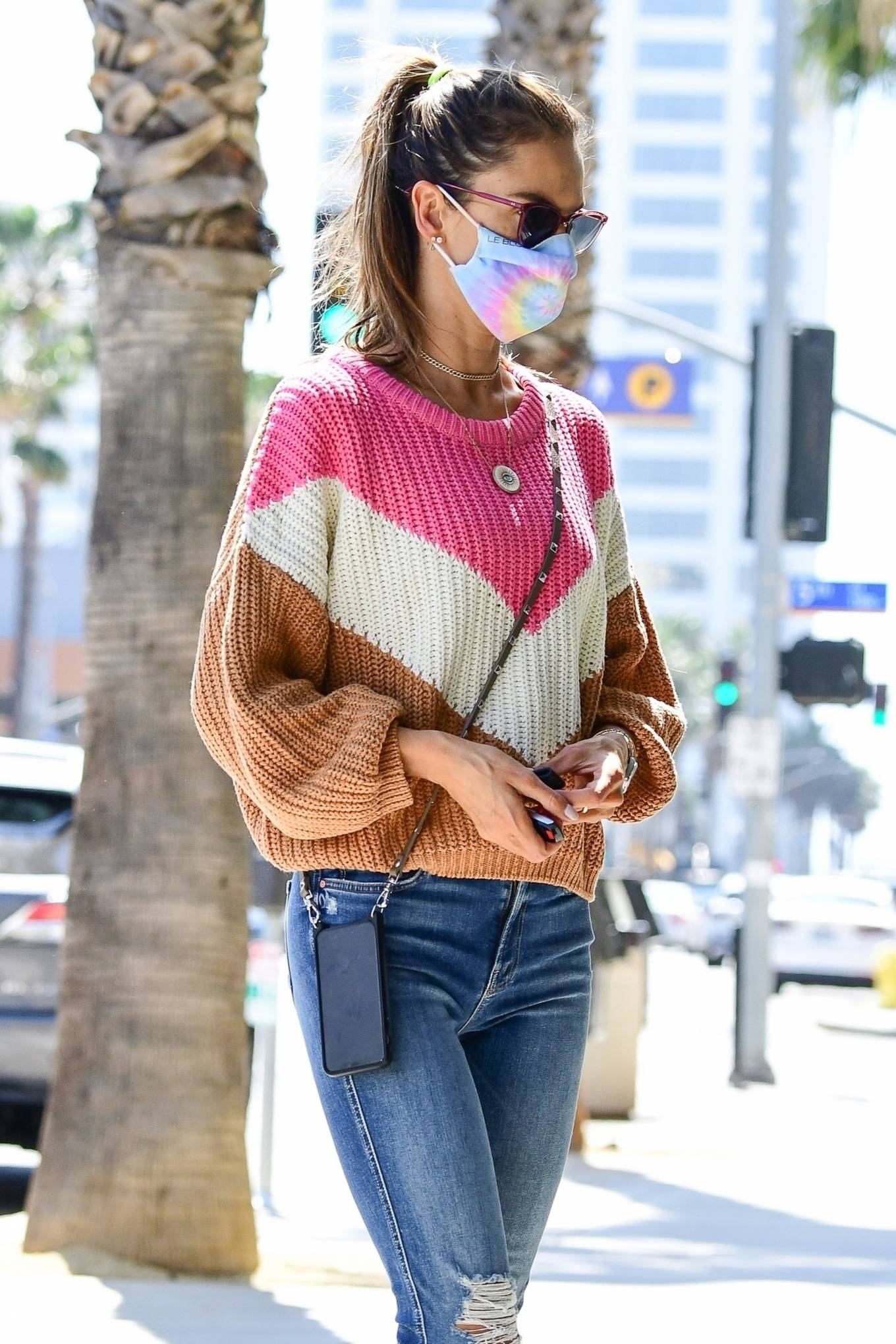 Alessandra Ambrosio, tan sneakers, black sunglasses, oversized sweater, round, lace-up, flat heel, brown sneakers, distressed blue jeans. Alessandra Ambrosio rocking round tan brown lace-up sneakers with flat heel