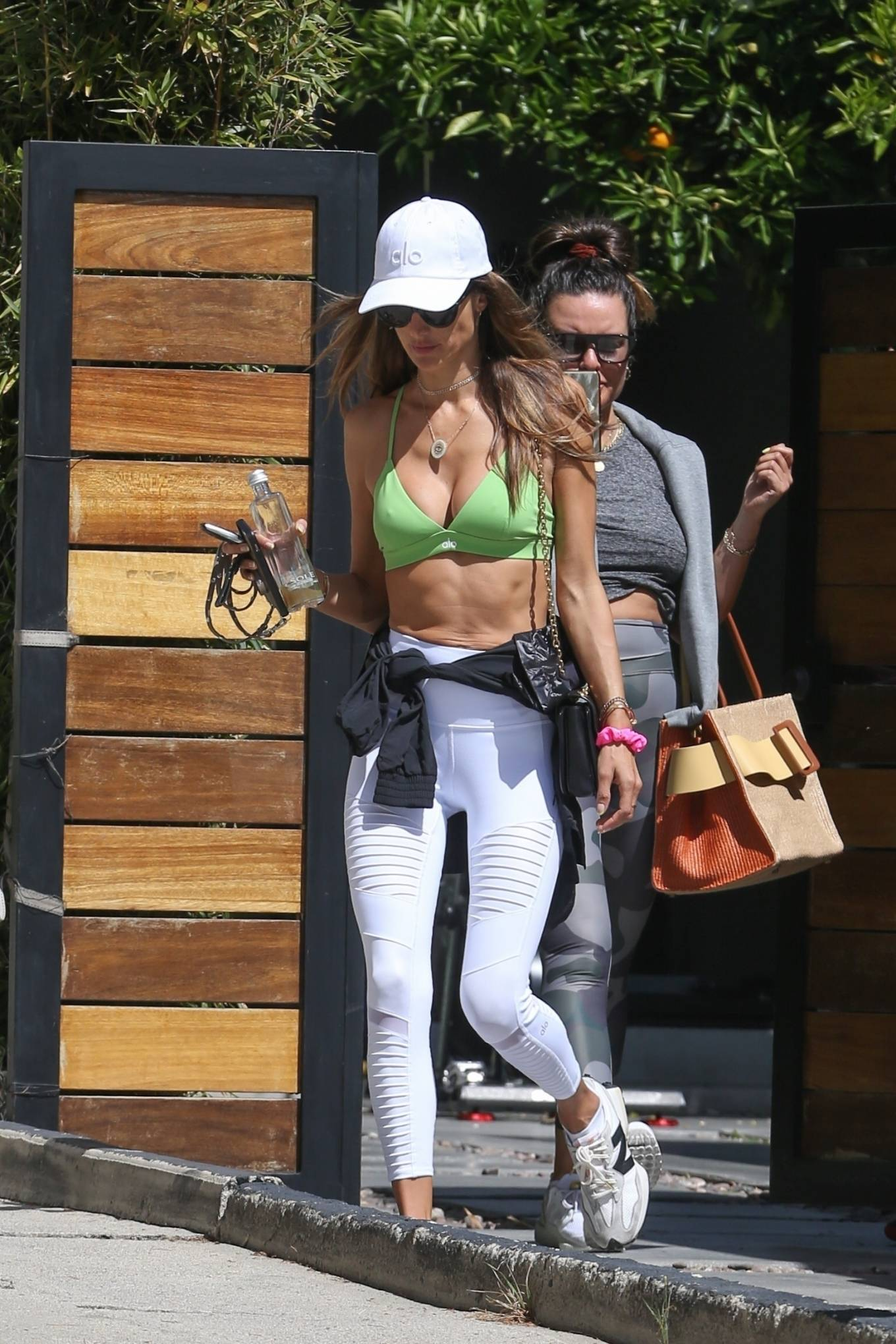 Alessandra Ambrosio donning a plunging green bralette with criss cross back, brand logo and spaghetti straps