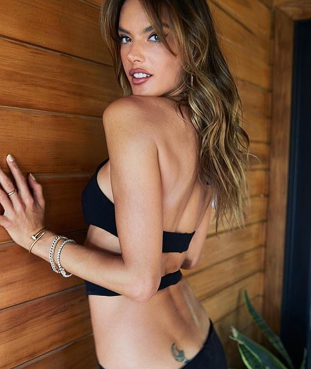Alessandra Ambrosio donning a figure hugging black dress with a cotton material, cut out waist and a halter neck