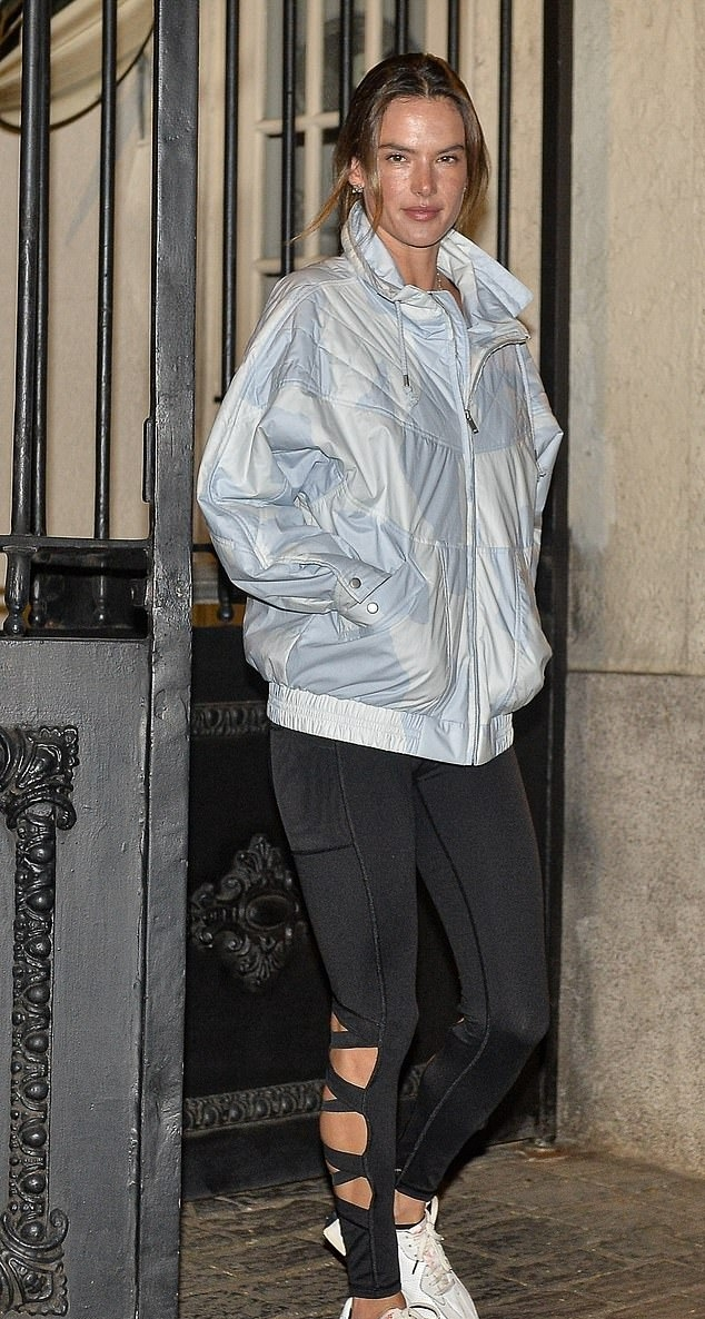 Alessandra Ambrosio rocking brand logo white and black lace-up sneakers by New Balance with flat heel