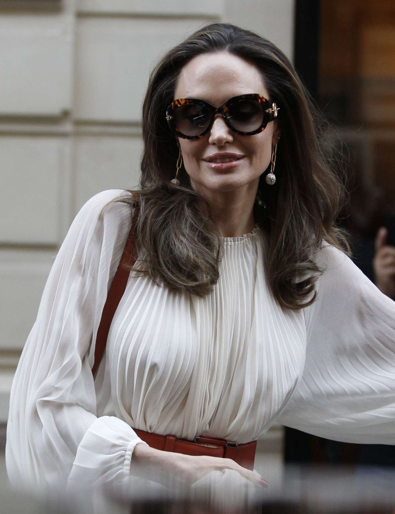 Angelina Jolie, Nude pumps, leather, black Louis Vuitton sunglasses, off white The Row dress, narrow, pointy, high heel. Angelina Jolie donning pointy Nude leather pumps with high heel