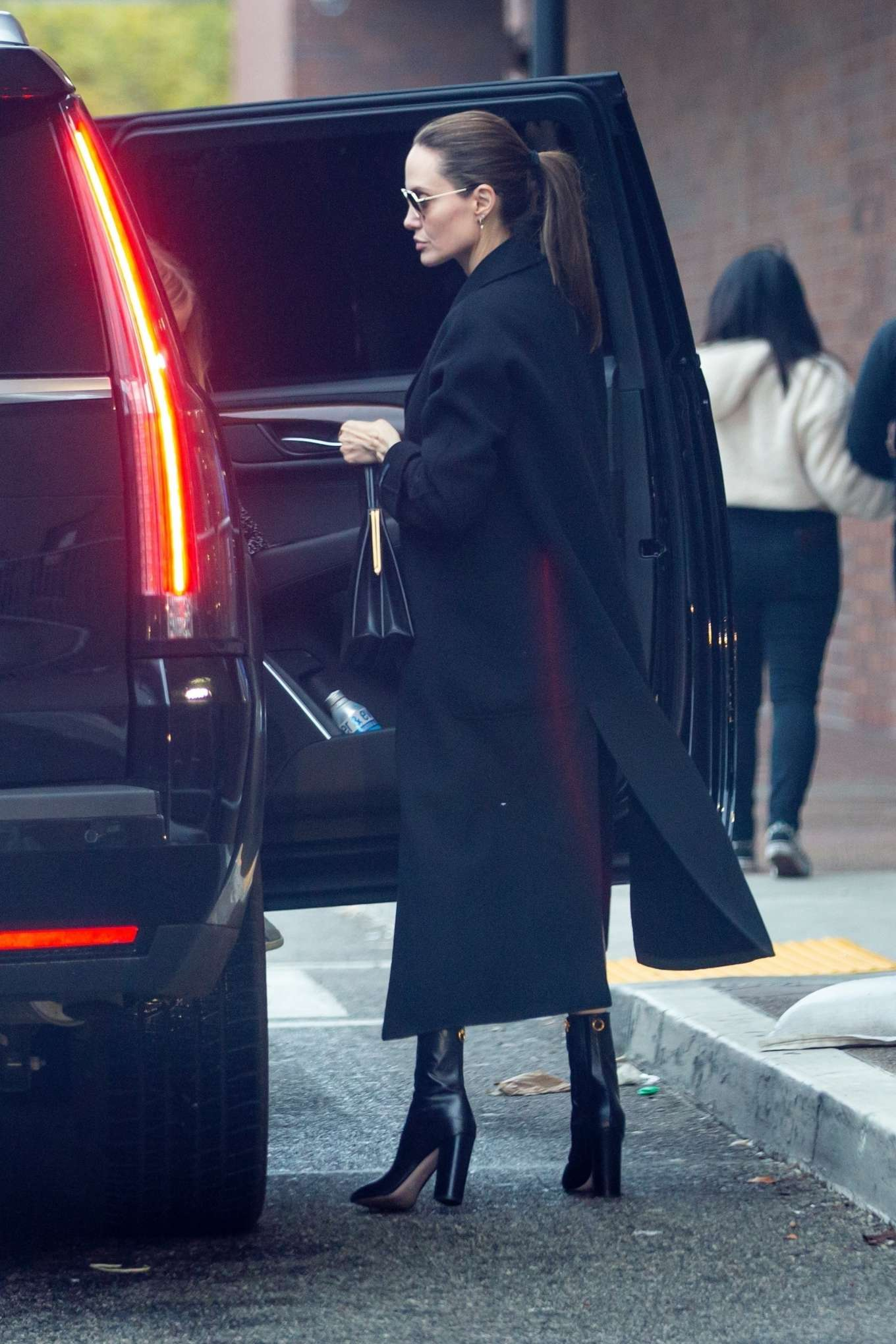 Angelina Jolie wearing pointy black leather ankle boots with high block heel